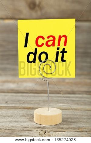 Yellow note paper on a holder on grey wooden background, i can do it