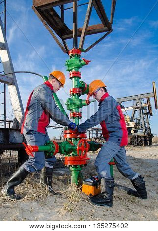 Workers in the oilfield repairing wellhead with the wrench. Pumpjack and wellhead background. Oil and gas concept.