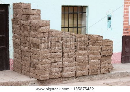 Adobe bricks stacked against house on rural street