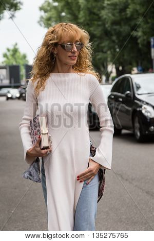 MILAN ITALY - JUNE 18: Fashionable woman poses outside Miaoran fashion show building during Milan Men's Fashion Week on JUNE 18 2016 in Milan.