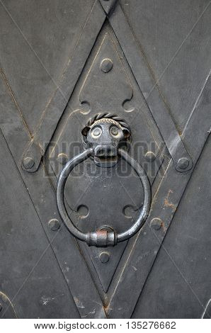 A fragment of an old metal door with a stylized animal head holding a ring.