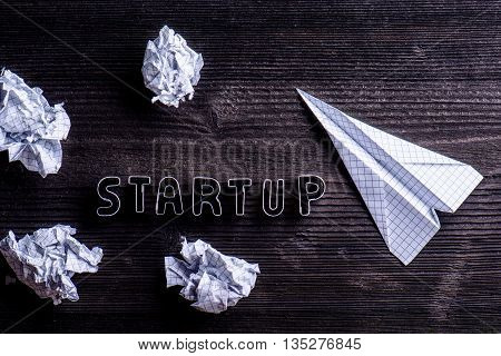 Desk, Start Up Sign, Airplane And Crumpled Paper Balls