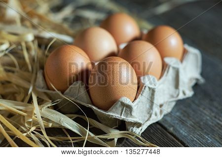Fresh farm brown eggs in a gray carton on a wooden rustic background