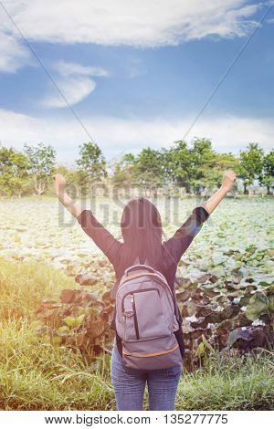 Women back or rare view with focused backpack on natural pond and puffy clouds sky view women raise or stetch two arms relax at the pond