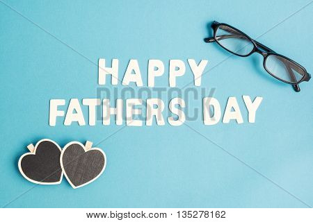 Happy Father's Day - Top view of white Happy Father's Day wording with black eye glasses and two heart shape on light blue background - Happy Father's Day pastel color