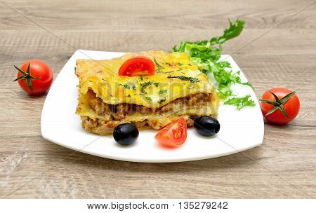 Lasagna with minced meat on a white plate on a wooden background. horizontal photo.