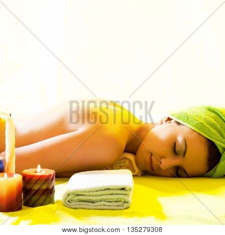 Beautiful woman lying down with towel on her head getting ready for the spa treatment
