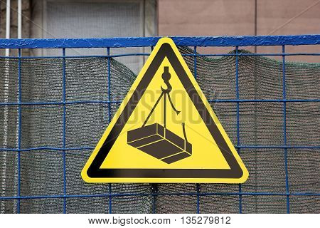 traffic construction yellow triangular sign warning about falling weigh from height on construction site