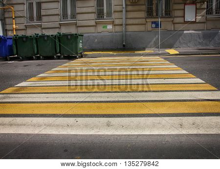 white and yellow lines pedestrian crossing on asphalt and green garbarge dumpsters on street of Moscow Russia