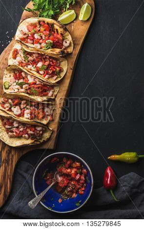 Shrimp tacos with homemade salsa, limes and parsley on wooden board over dark background. Top view, copy space. Mexican cuisine