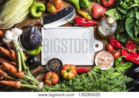 Fresh raw vegetable ingredients for healthy cooking or salad making with white ceramic cutting baoard in center, top view, copy space. Olive oil, spices and knife. Diet or vegetarian food concept