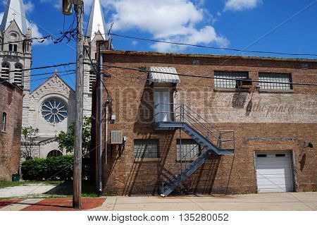 JOLIET, ILLINOIS / UNITED STATES - JUNE 1, 2015: A metal stairway leads the second floor of an old brick building in downtown Joliet.