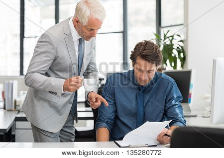 Senior business man talking with young worker in office. Business people with computer sitting at office and consulting. Senior managing holding a cup of coffee guiding employee on report.