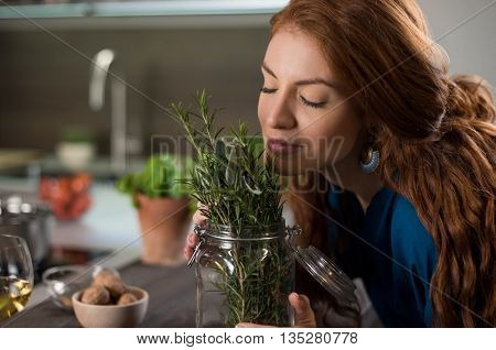 Happy young woman enjoying the fragrance of plants. Young woman energizing herself with plant smell. Portrait of woman smelling rosemary and sage with eyes closed.