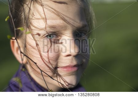 windy hair strands on child girl face by springtime and tiny tree branch