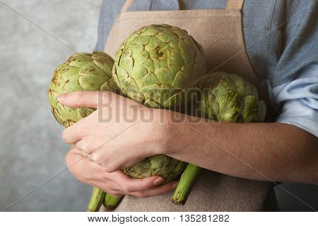 Woman holding few artichokes
