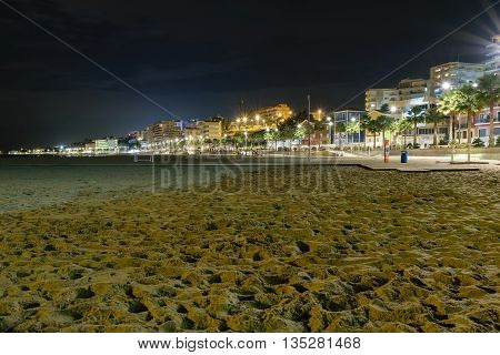 Beach and cityscape of the multicolored and famous town Villajoyosa at night at the Mediterranean Sea at the Costa Blanca in Spain.