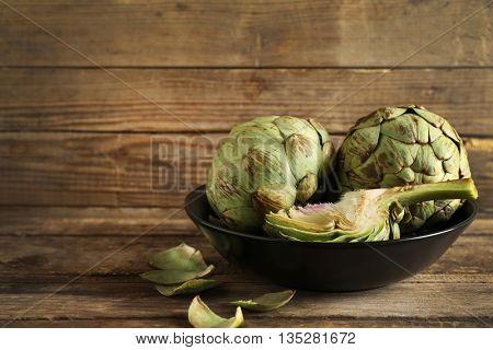 Artichoke on plate on wooden background