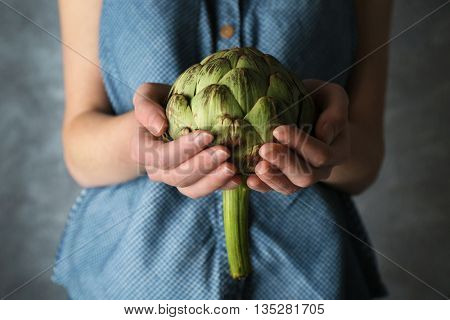 Woman holding artichoke