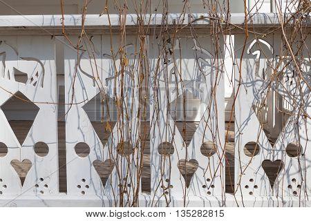 Thread on white wooden veranda with vine brunches