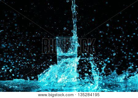 Pouring water into glass on black background