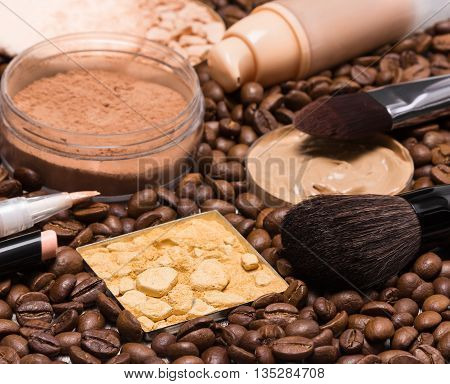 Basic makeup products to create beautiful skin tone and complexion. Concealers, liquid foundation, compact, loose and shimmer golden powder with brushes on coffee beans. Focus on the front brush