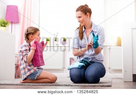 mother and daughter cleaning up room
