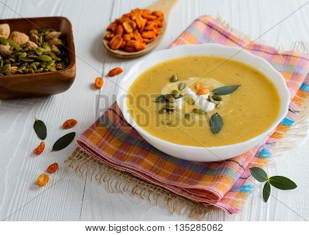 Cream soup with pumpkin sunflower seeds on a white wooden background with leaves