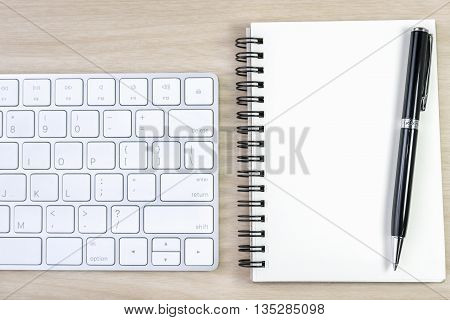 blank notebook and pen with keyboard on wooden table writing concept