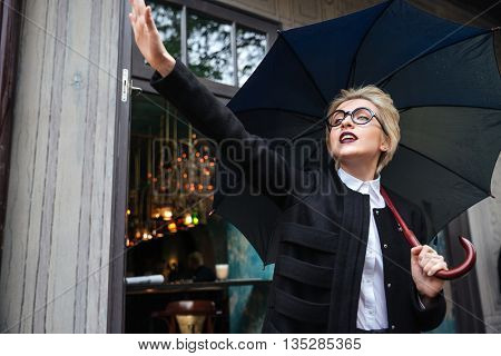 Young beautiful woman with umbrella waving outdoor standing at cafe
