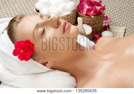 Portrait of young beautiful woman in spa environment girl with shiny skin of face in towel relaxing