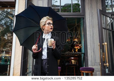Young beautiful woman with umbrella and coffee cup outdoor standing at cafe