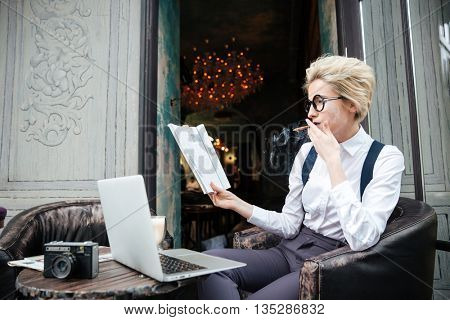Pensive young woman with cigarette using laptop and reading magazine in cafe
