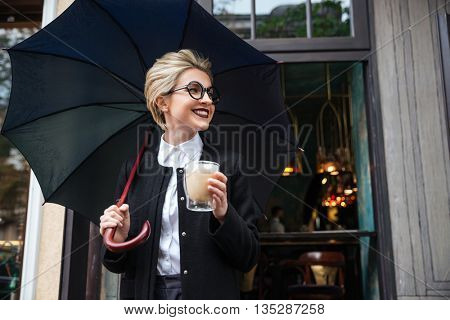 Young smiling beautiful stylish woman with umbrella and coffee cup