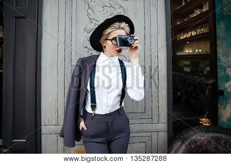 Focused young woman photographer standing and taking pictures using photo camera