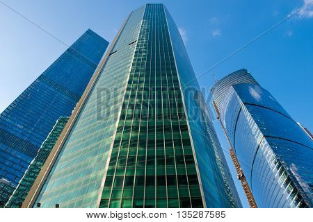 Steel and glass corporate buildings reflect the sky and clouds Moscow