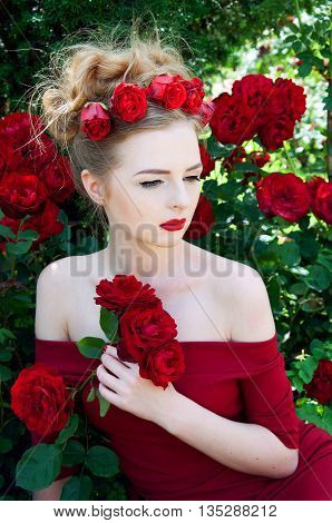 Lady vamp in crimson red dress with naked shoulders and red roses in her hair