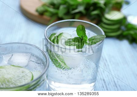 Infused lime water with cucumber on wooden background