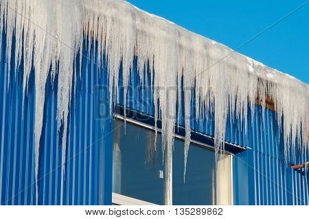 Large icicles hanging from the roof after the thaw