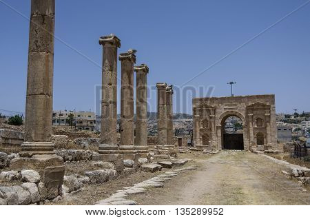 Columns In Colonnaded Street And North Gate At Background, Ancient Roman City Of Gerasa Of Antiquity