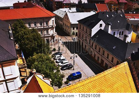 2016/06/18 Chomutov city Czech republic - cobbled square 'Husovo namesti' with a small parking area and large deciduous trees before the start of the summer tourist season