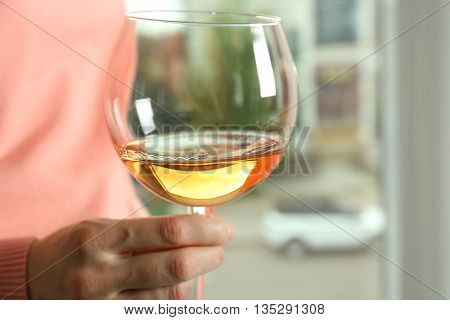 Female hand holding glass of  white wine on blurred background