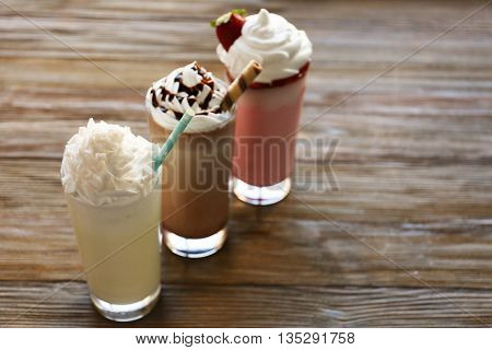 Delicious milkshakes on wooden table