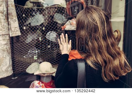 Attractive brunette window shopping. Chosing a new hat.