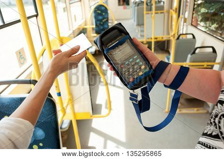 Human hand holding plastic cards. Passenger pays for the fare in public transport. Payment terminal credit card reader sales concept.