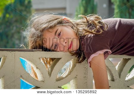 A young tween girl lays across a wall on a lazy day. She is relaxing and soaking in the sun.
