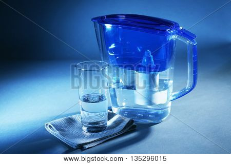 Filter and glass of water on dark blue background
