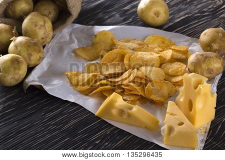 Potato chips, raw potato and cheese on wooden background.