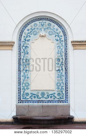 architectural arch on the facade of the building with blue stucco with space for text.