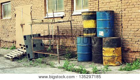 Old dirty barrels of oil under in the industrial zone